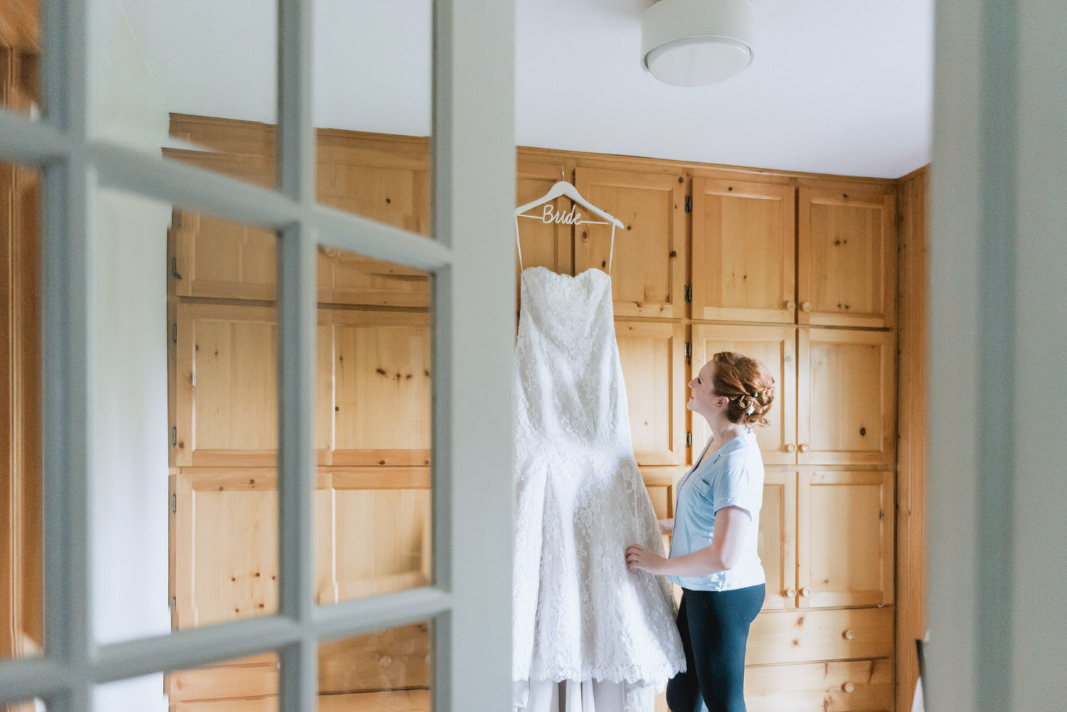 Bride staring at her wedding dress hung on a wall
