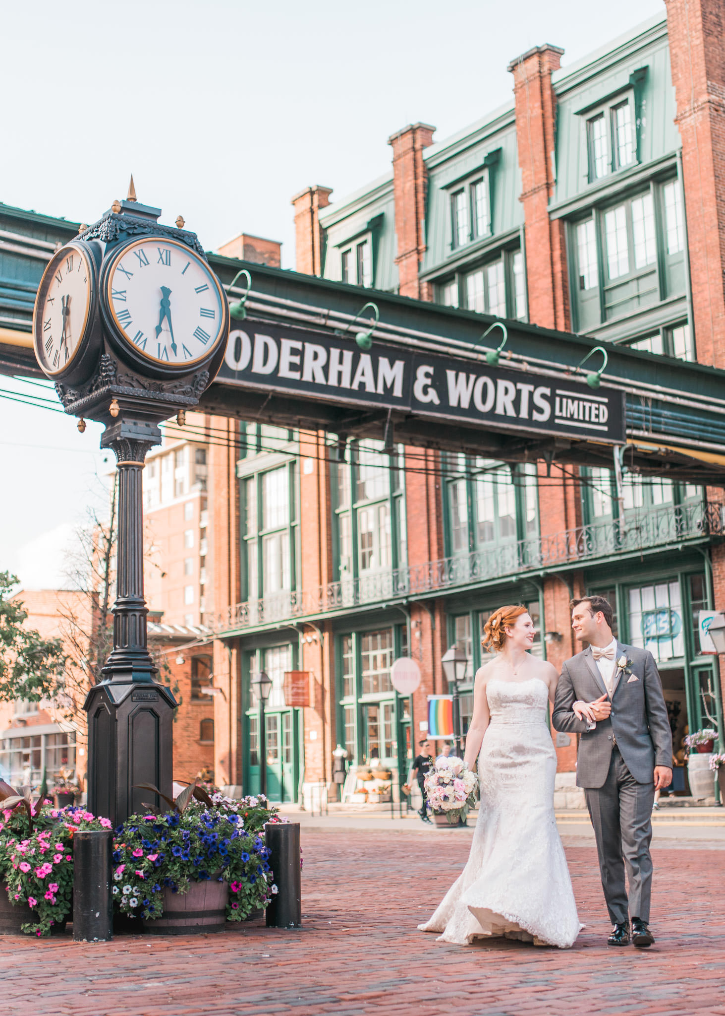 Groom and bride walk in the distillery district in Toronto wedding
