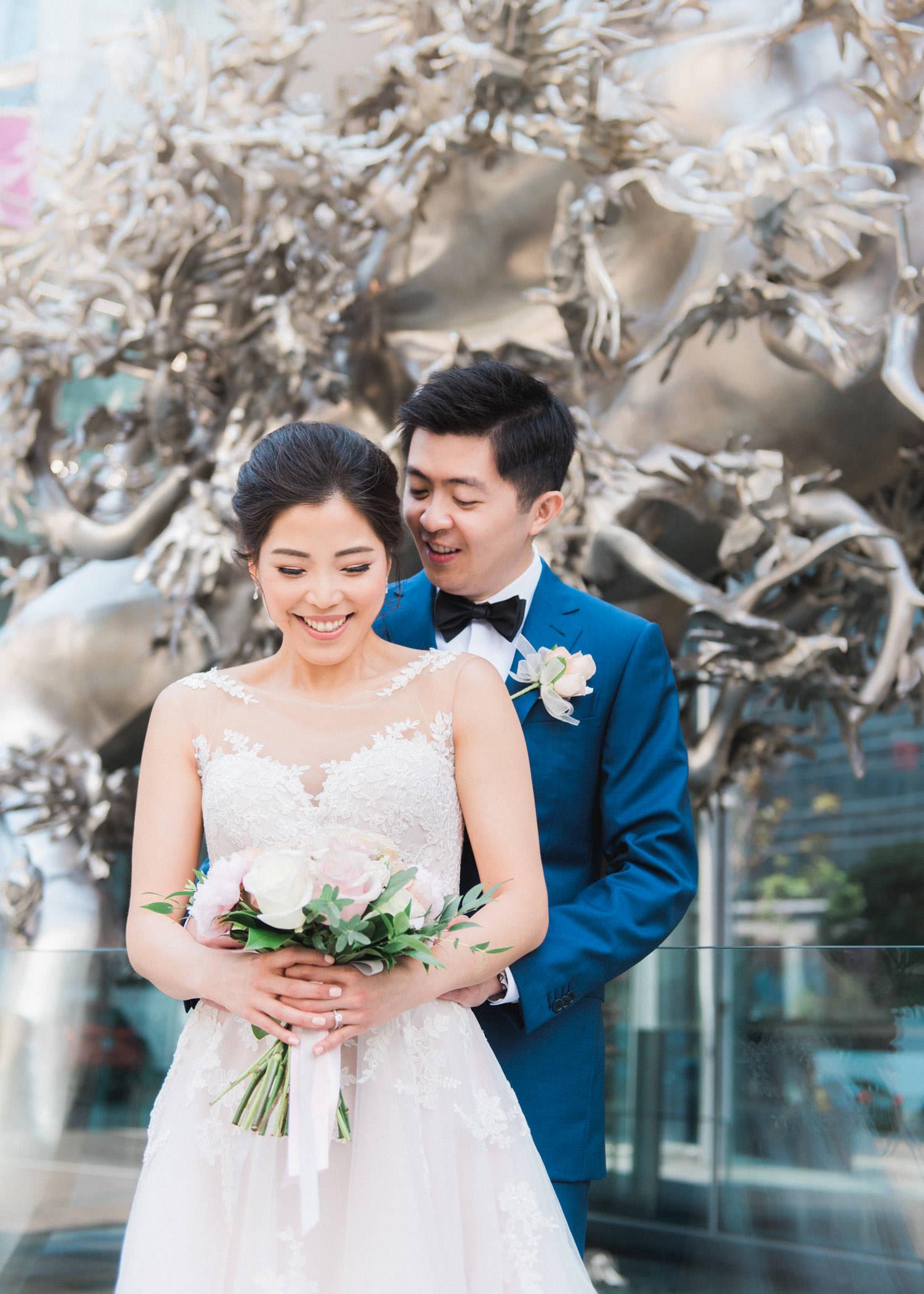 Bride and groom pose outside iconic statue of Shangri-La Hotel in Toronto