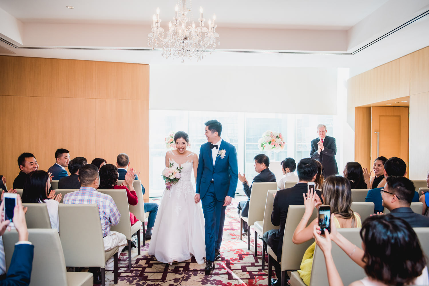 Groom and bride exit ceremony while crowd cheers at Shangri-La Hotel in Toronto