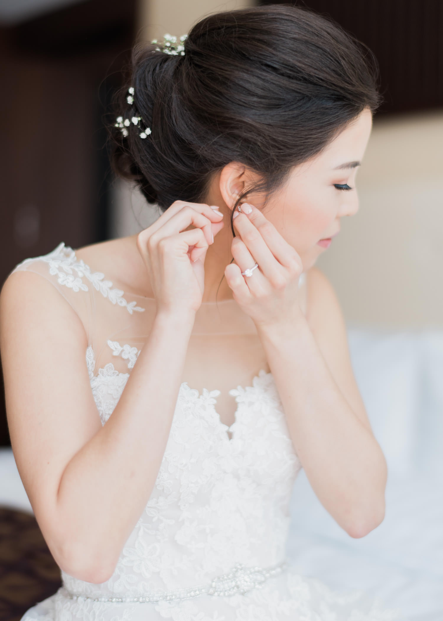 Bride putting on her earrings at Shangri-La Hotel in Toronto