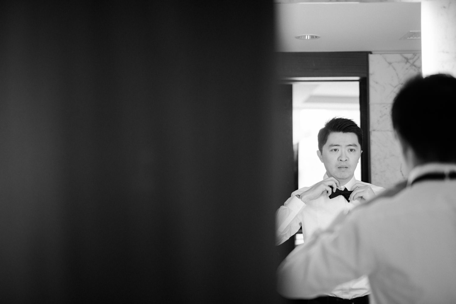 Groom tightening bow-tie at Shangri-La Hotel in Toronto
