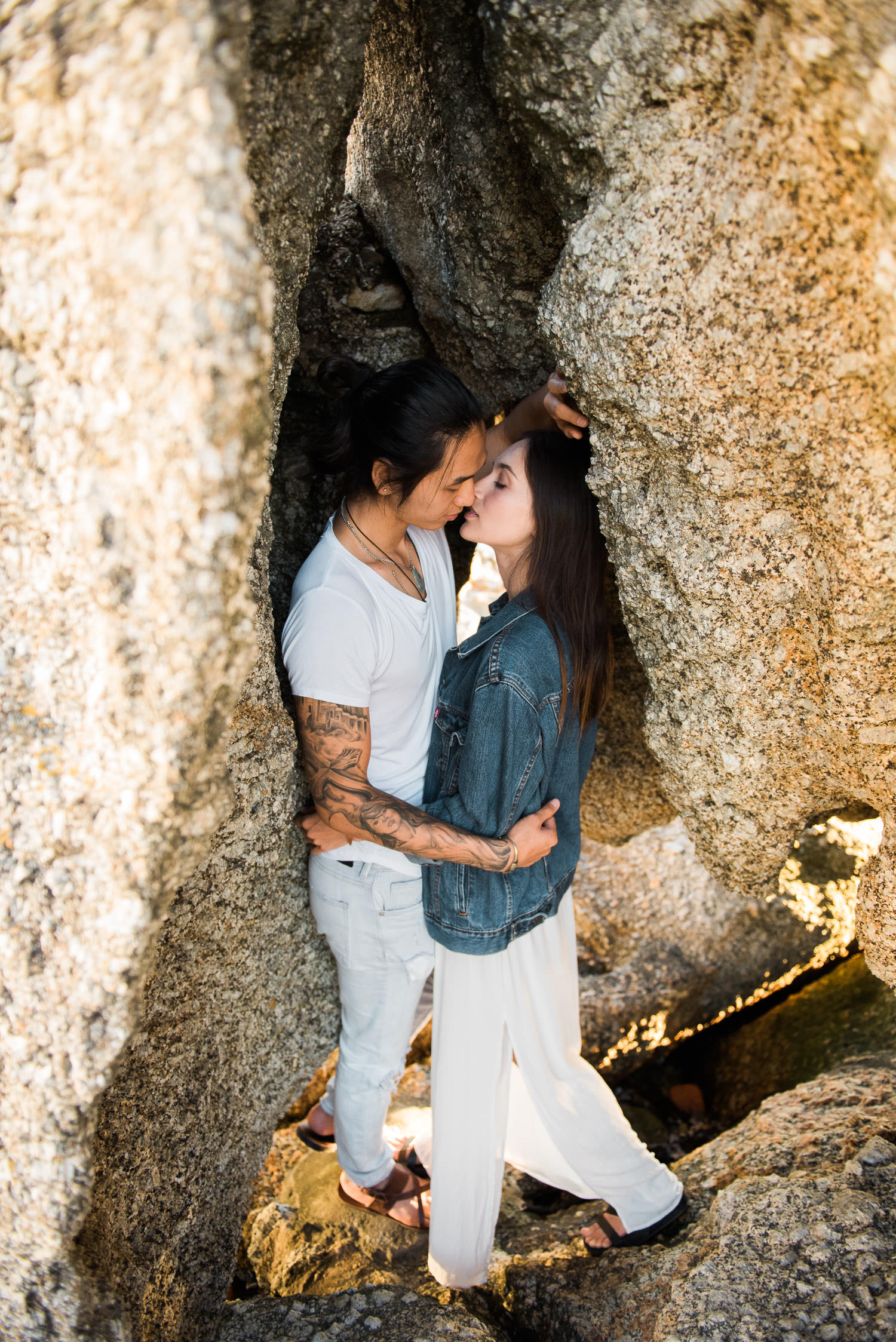 Couple share a kiss beneath boulders during engagement shoot in Cape Town