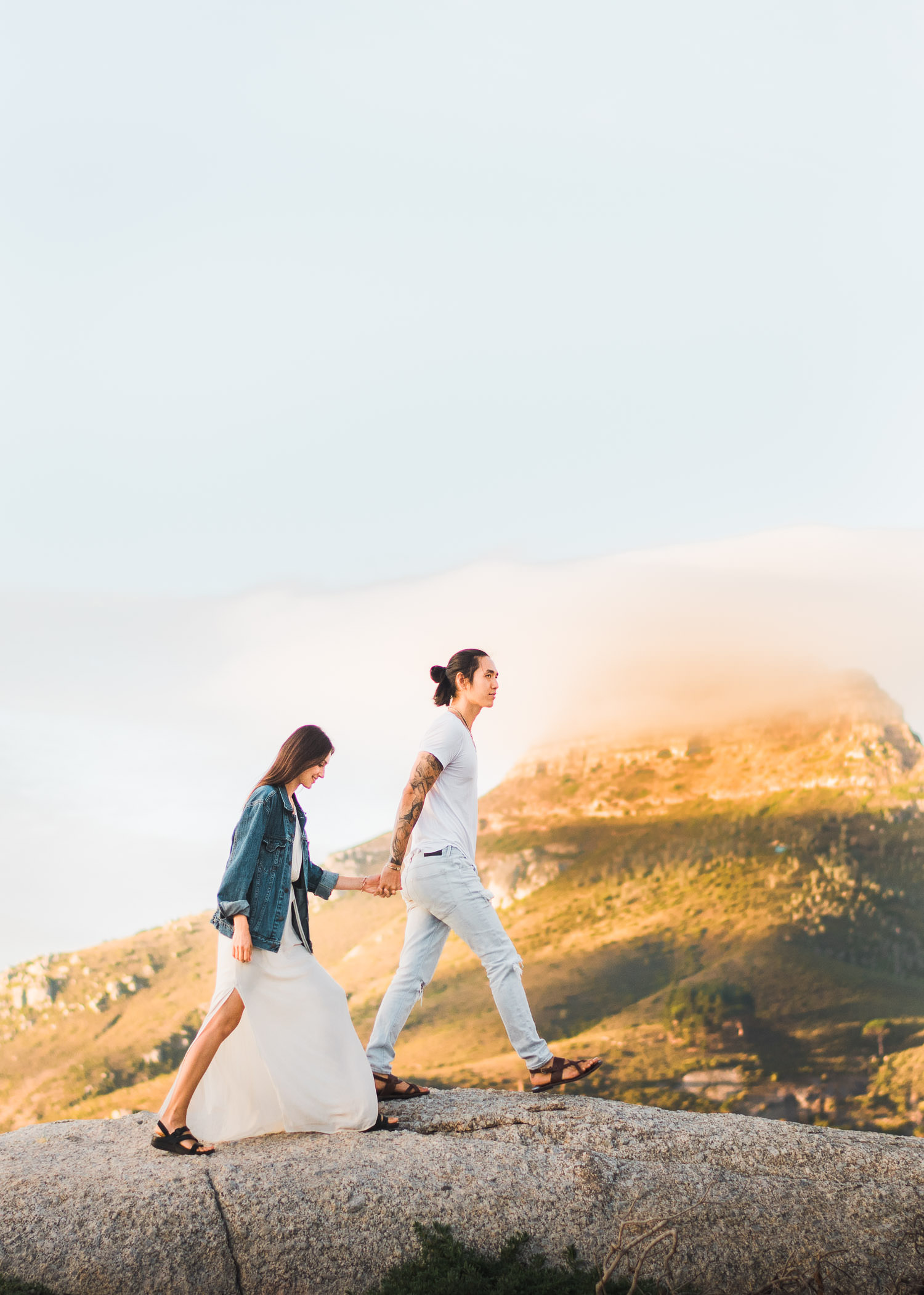 Couple holding hands, walking towards Lion's Head in Cape Town engagement session