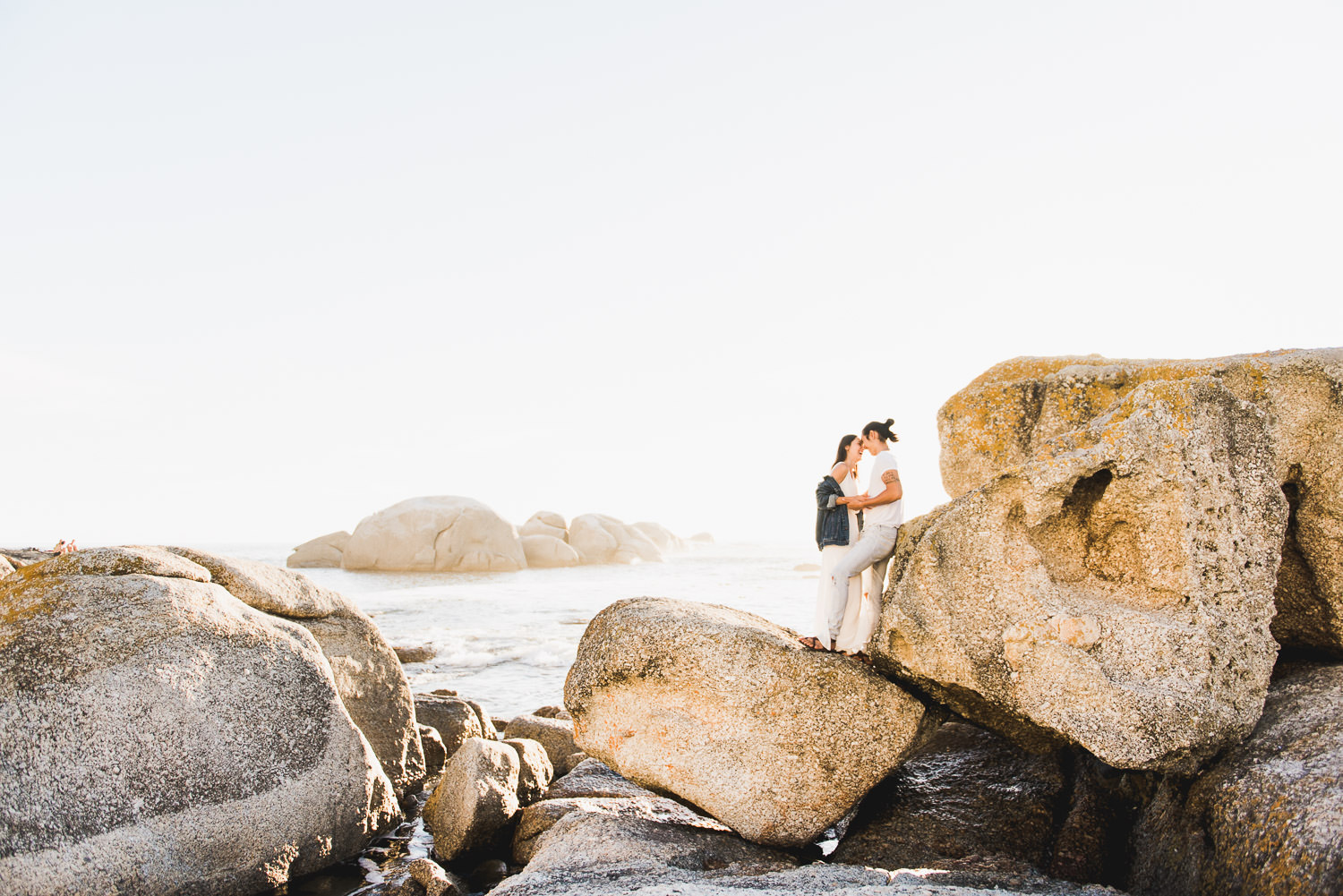 Wide shot of couple posing on boulders during sunset a Cape Town engagement shoot