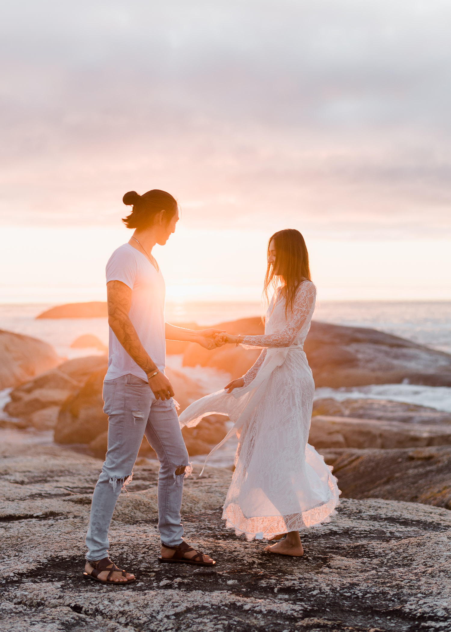 Couple dancing on rocks at sunset during Cape Town engagement session