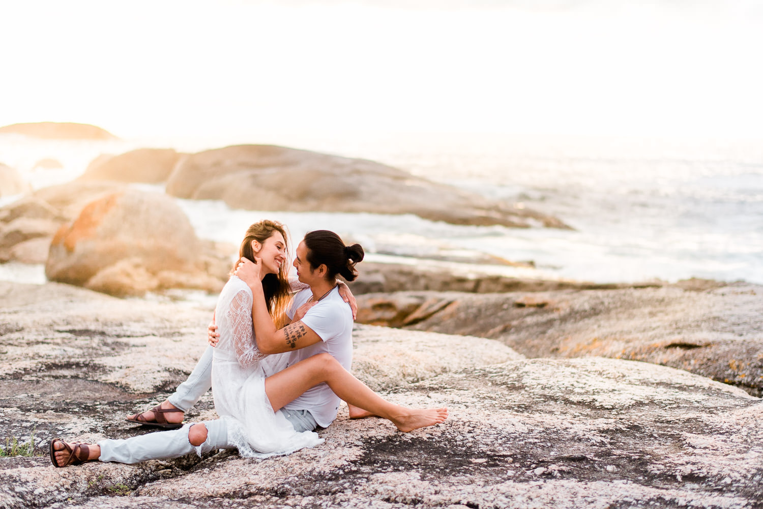 Sexy couple sitting on each other on boulders during sunset in Cape Town engagement shoot
