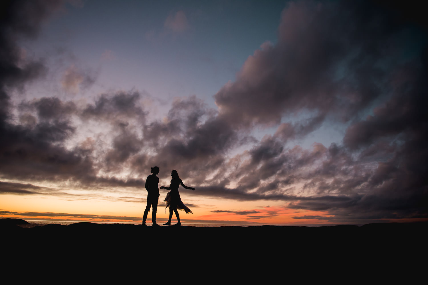 Couple dancing at sunset in Cape Town's Atlantic ocean