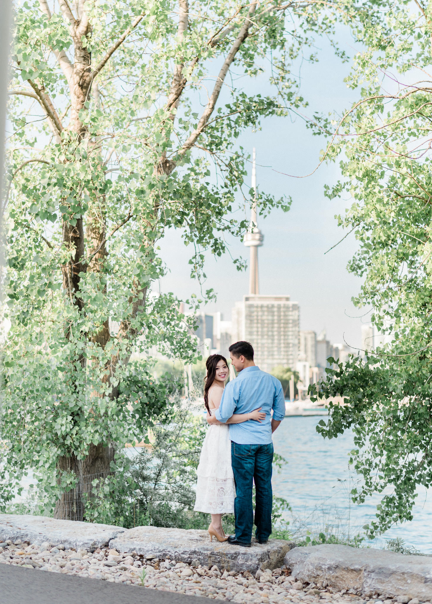 Couple staring at the CN tower from Trillium Park during an engagement shoot in Toronto