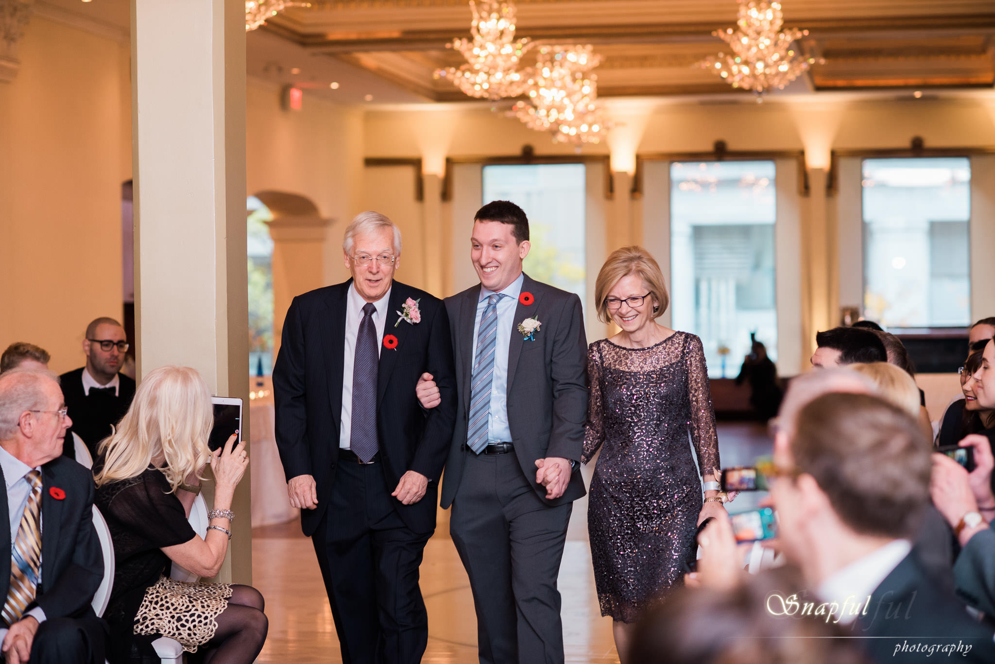 groom is accompanied by his parents down the aisle at the Rosewater in Toronto