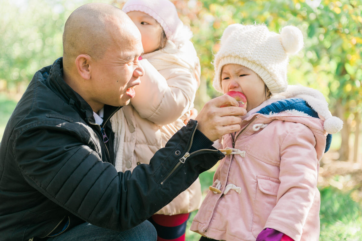dad holding up apple for daughter to bite