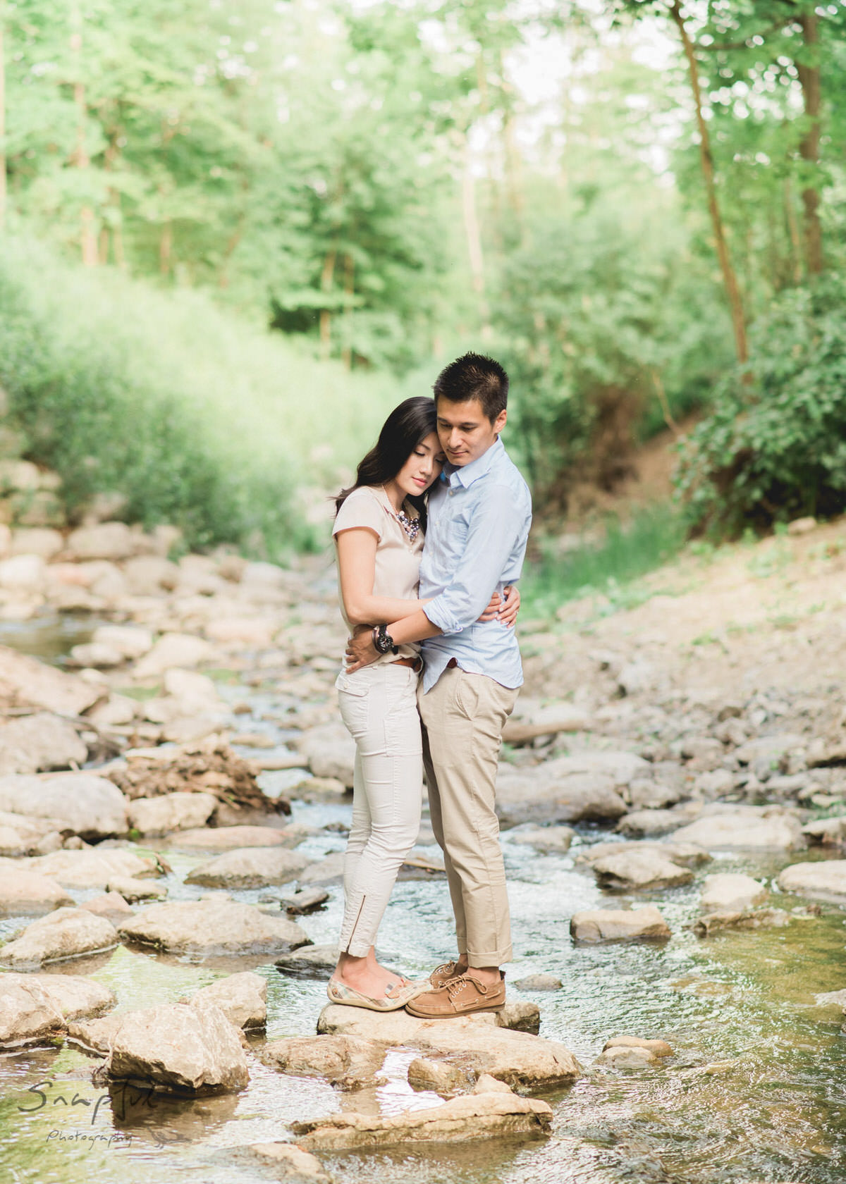 Couple sharing an intimate moment on a rock in a river