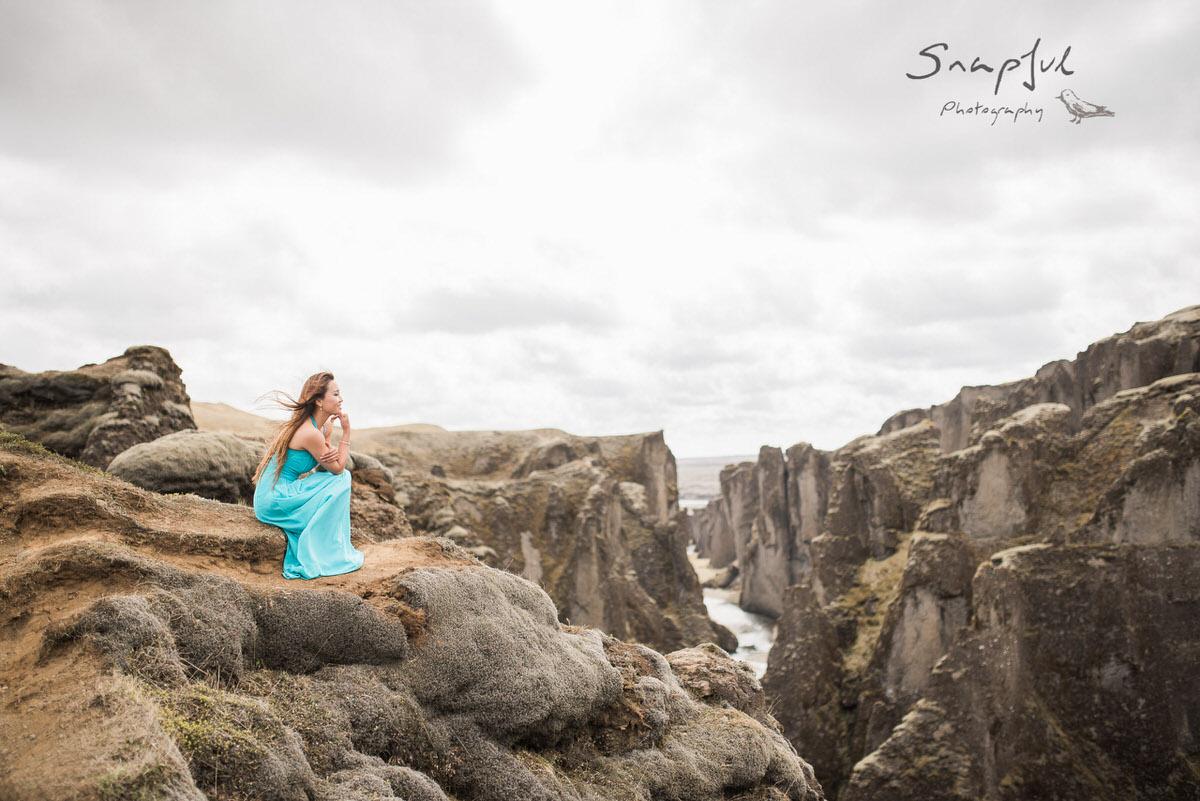 Woman in blue dress sitting on rocks at Fjaðrárgljúfur canyons