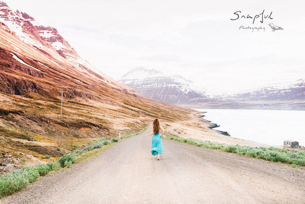 Woman running on the road towards Seyðisfjörður