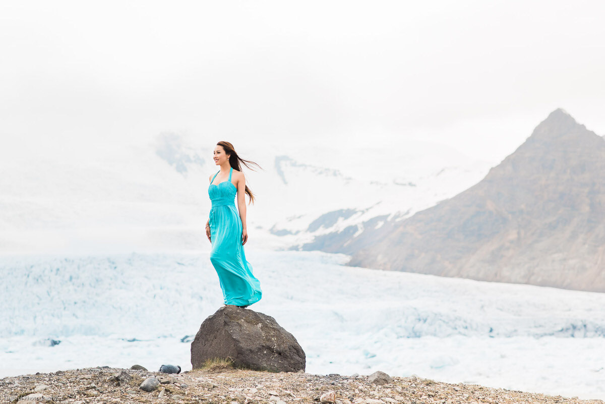 Girl in blue dress standing in front of a glacier