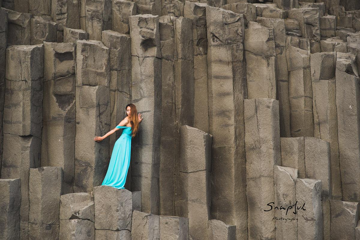 Woman standing on basalt column at reynisfjara