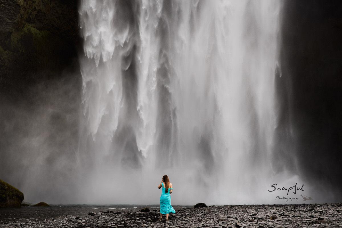 Girl in a blue dress running towards Skogafoss