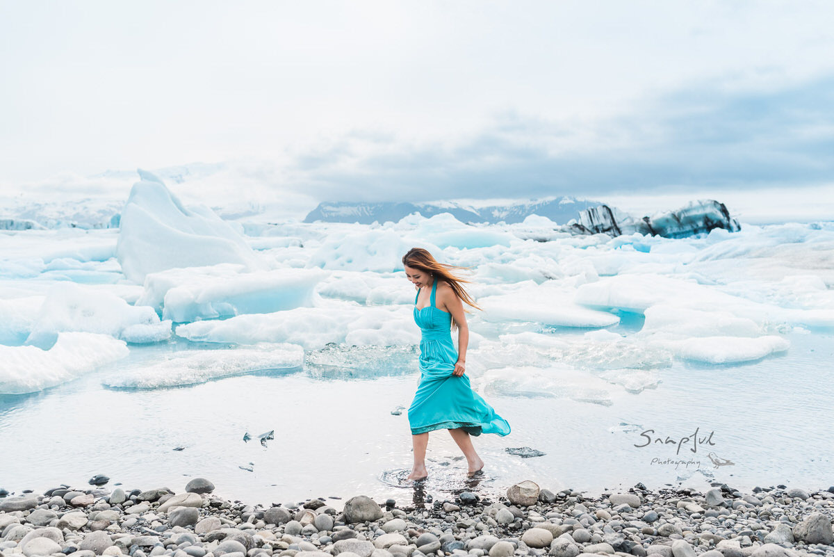 Woman in blue dress walking in the water at Jökulsárlón Glacier Lagoon